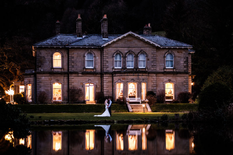 Harkness Grange by night with a bride and groom stood outside
